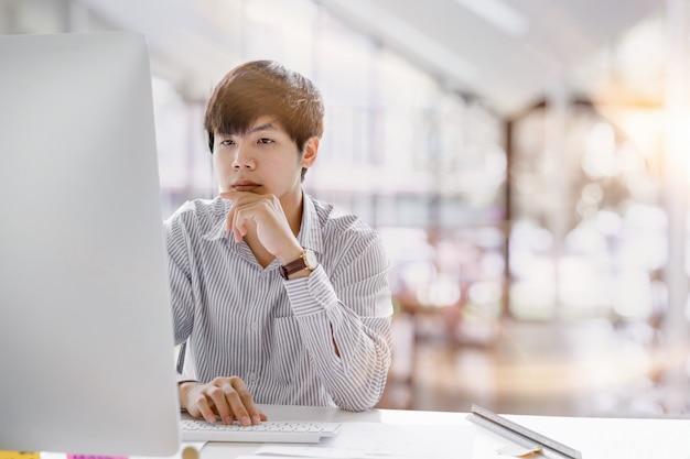 コワーキングスペースでラップトップに入力して考え、集中している深刻なアジア系のビジネスマンのショットをトリミングしました。男ラップトップ作業コンセプト