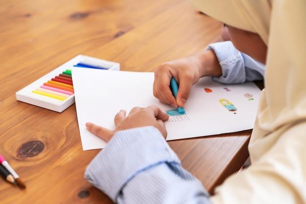 学校で絵を楽しんでいるかわいいイスラム教徒の少女。教育、学校、芸術、絵画のコンセプト