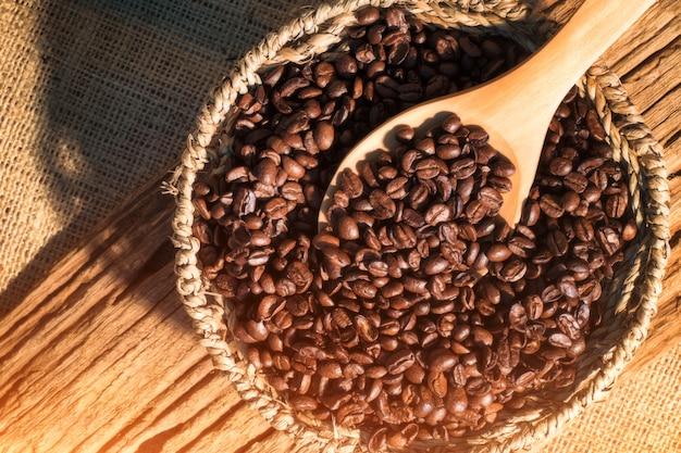 コーヒー豆のバスケットの上のコーヒー豆の木のスプーン。マットスタイル、ビンテージスタイル。