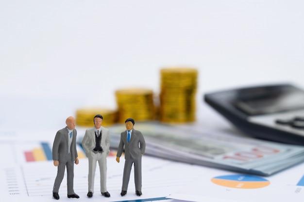 ビジネスレポートグラフ上に立っている共同投資ビジネス人々のミニチュアモデル