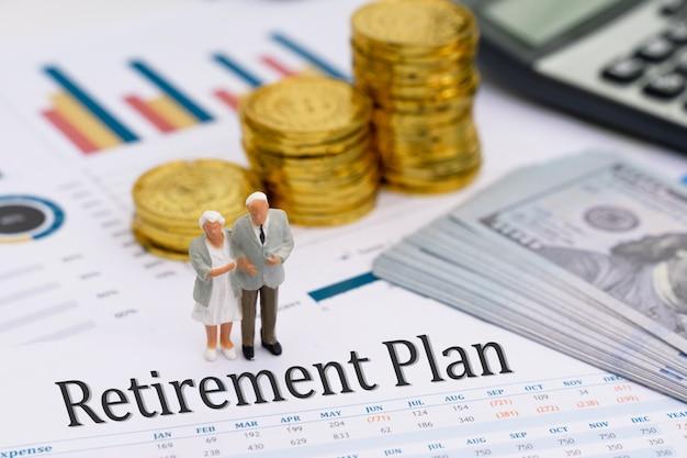 退職後の計画レポートの上に立って年配のカップルのミニチュアモデル