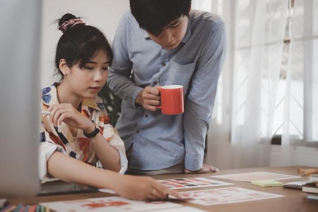 若いアジアの創造的なモバイルアプリケーション開発者チームワークの創造的な計画のモバイルアプリケーション開発のためのモバイルテンプレートデザイン画面での議論。