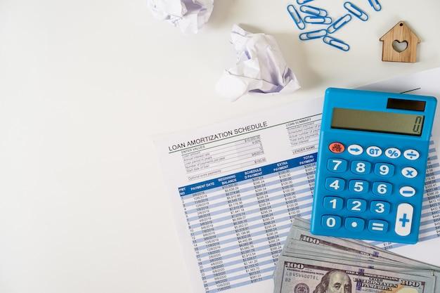 個人的な財務計画のコンセプトローンスケジュールシート、私たち紙幣、電卓、フラットホワイトバックグラウンドの上に置きます。