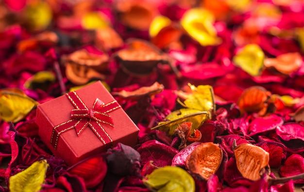 赤いリボンと結ばれた赤いギフトボックスと乾いた花の弓