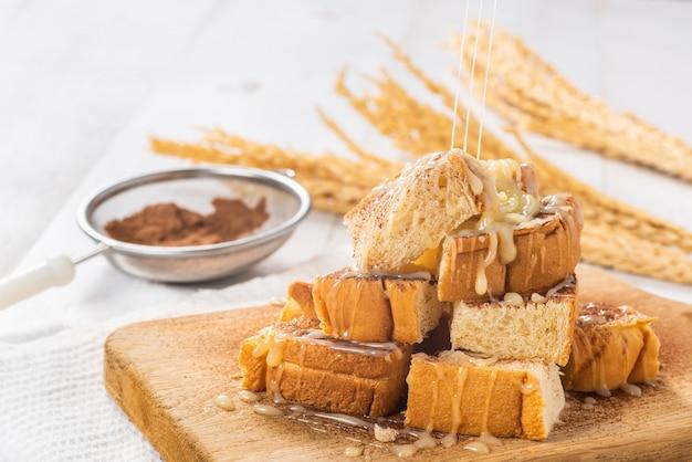 Сгущенное молоко с сахаром, льющееся в груду хлеба на деревянной разделочной доске