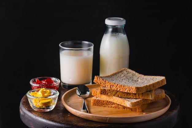 円形の木製テーブルにミルク、バター、いちごジャムとパンのスタック