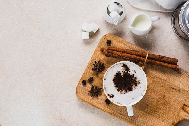 牛乳、砂糖、アニス、シナモンロールとコーヒーのカップは、テラゾー石のテーブル、コピースペースでトップビューで提供しています