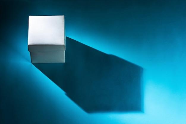 Белая коробка на синем фоне с тенью