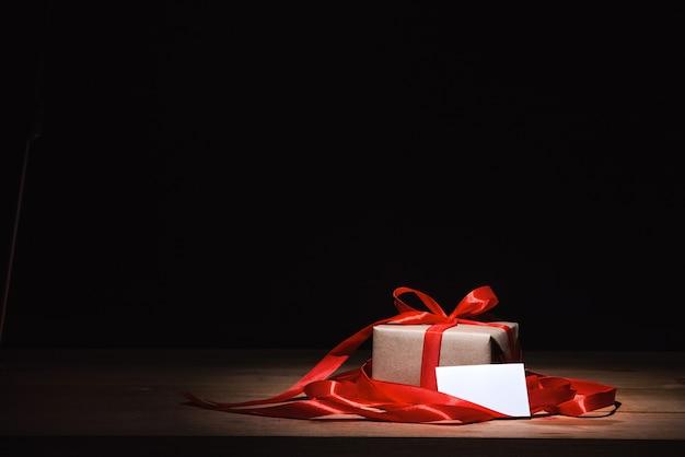 赤いリボンと白いカードで結ばれたクラフトギフトボックス