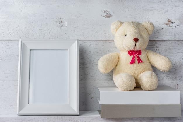 Белая пустая фоторамка на деревянной полке и стене, украшенная стопкой книг и куклой-мишкой