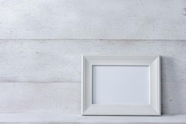 Белая пустая фоторамка на деревянной полке и стене