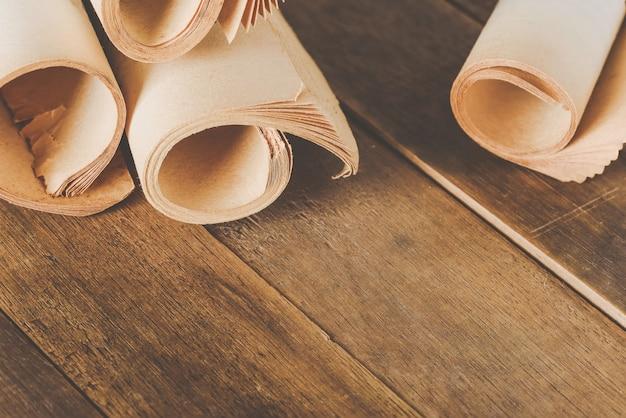 木製のテーブルの上の圧延の古い本のページのクローズアップ