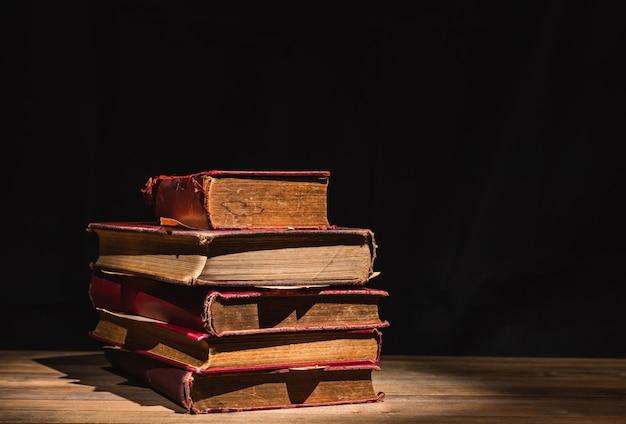 木製のテーブルの上の古い本の山
