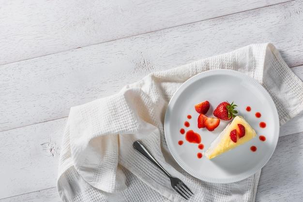 Кусок клубничного торта десерт и соусом на белом блюде, вид сверху