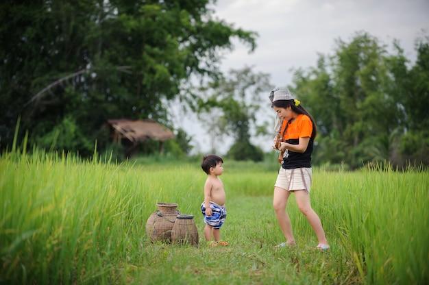 緑の田んぼで遊んでいる母とかわいい赤ちゃん、家族愛のコンセプト。