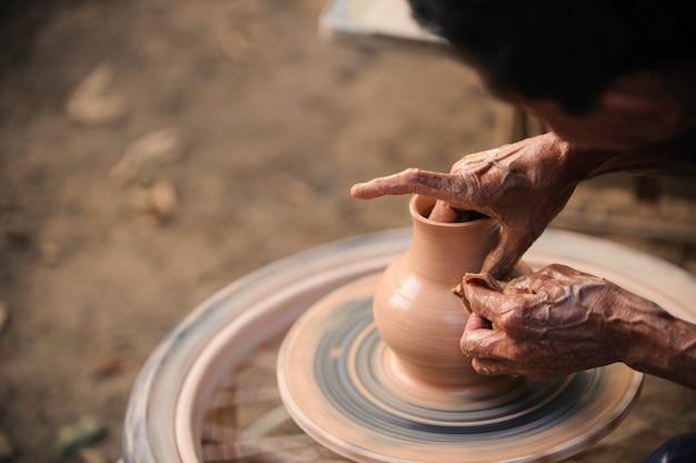 メカニック陶器を使用している専門のタイの老人は、タイで陶器を作った。