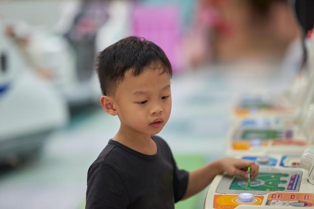少年は一人でアーケードゲームをプレイ