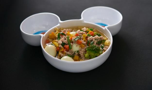 黒の背景に卵野菜と豚肉のスープ