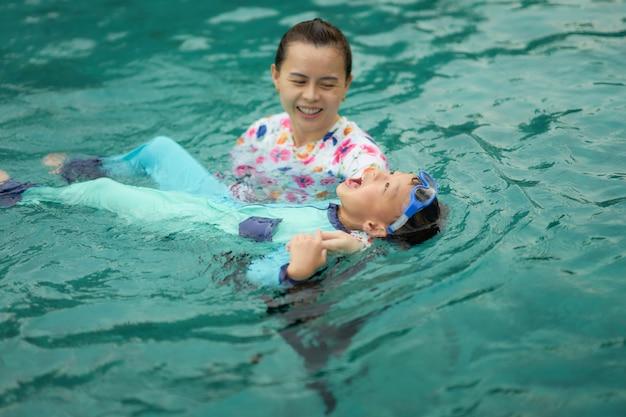 母は家族の活動休暇の概念で幸せにプールで泳ぐことを息子に教える