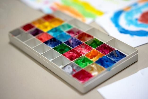 ワークスペーステーブル上の子供またはアーティストの芸術作品の複数のカラーパレット