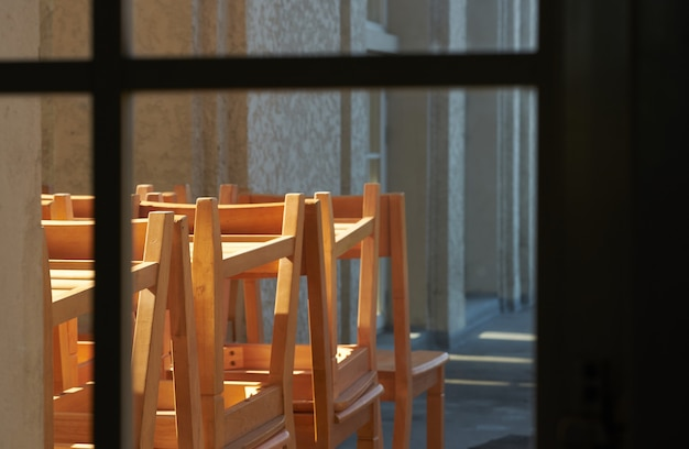Школьная сцена с кучей учебных столов и стульев хранится на веранде в память о старом школьном времени