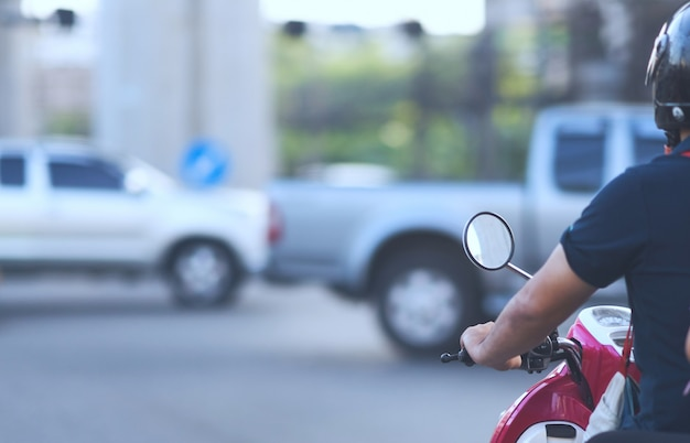 安全ヘルメットとの交差点で緑色のライトを待っているオートバイ