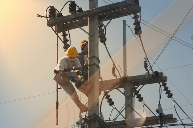 技術者は、高電圧電気ポールに取り組み、光を反射します