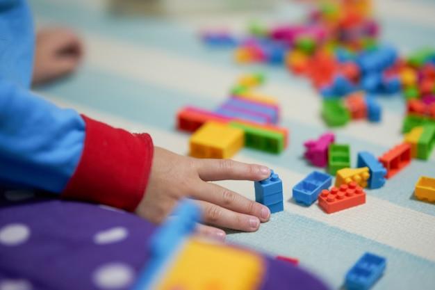 子供の手が遊ぶためのマットの床にカラフルなレンガのおもちゃに触れる