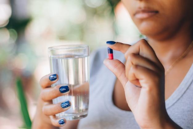 薬の錠剤と水のガラスを保持している病気の女性。薬を飲んでいます。人とセルフメディケーションの概念。健康治療。うつ病、不眠症、痛み