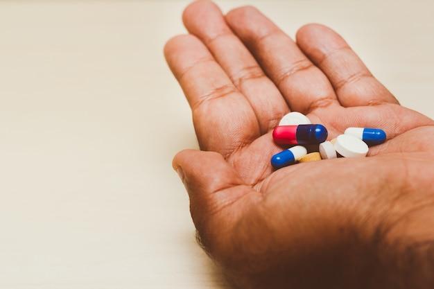 Капсулы медицины (ассорти таблетки) в мужской руке. светлый фон понятие о самолечении, здоровье, депрессия, рак, лекарства.