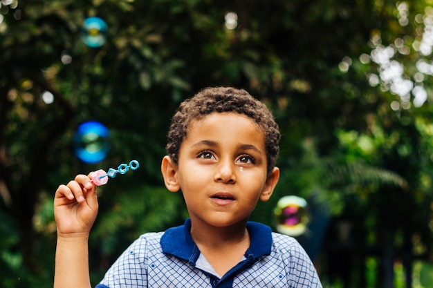 Улыбающийся мальчик играет мыльный пузырь