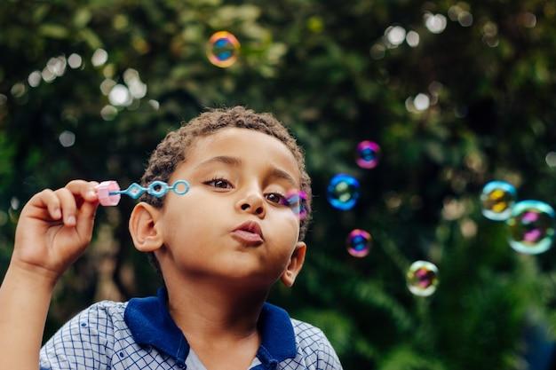 Мальчик играет мыльный пузырь