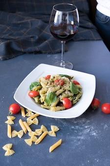 Паста с соусом песто, свежим базиликом и орехами на белой тарелке