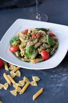 ペストソース、新鮮なバジル、白い皿にナッツのパスタ。濃い青色の背景にスパゲッティ