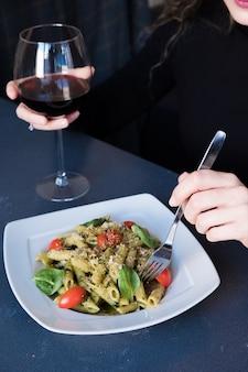 Девочка ест макароны с соусом песто, свежим базиликом и орехами на белой тарелке