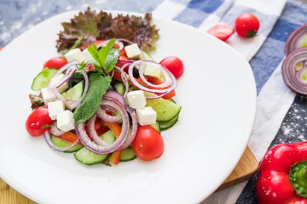 暗い石の背景に白い皿にギリシャ風サラダ。生鮮食品フラットを置きます。