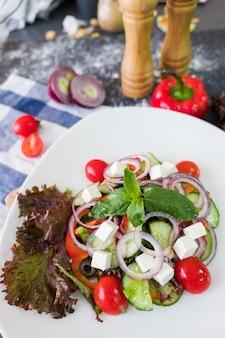 Греческий салат на белом фоне на фоне темного камня. свежая еда плоская планировка.