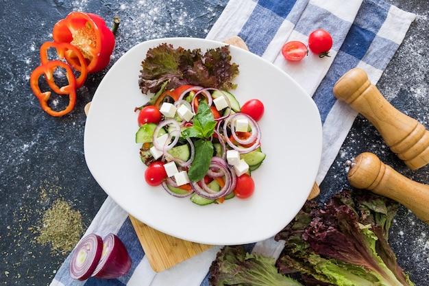 暗い石の背景に白い皿にギリシャ風サラダ。
