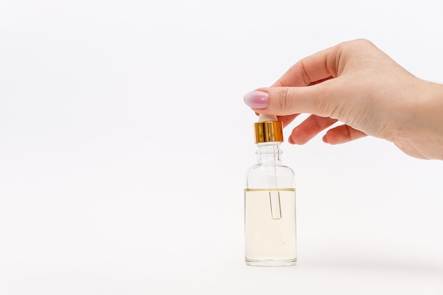ドロッパーガラスボトルモックアップ。油性ドロップが白い背景の上の化粧品のピペットから落ちる