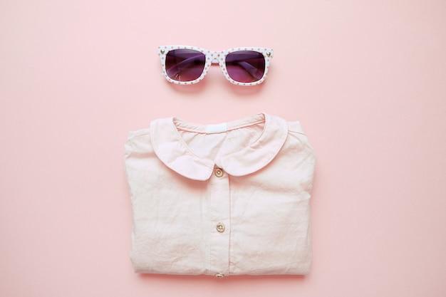 ピンクの背景に夏子供服のセットです。女の赤ちゃんのファッションに見えるシャツとメガネ