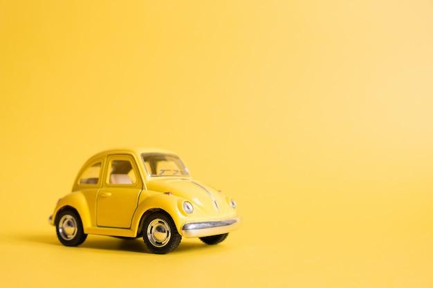 Желтый. ретро игрушечный автомобиль на желтом. концепция летних путешествий. такси