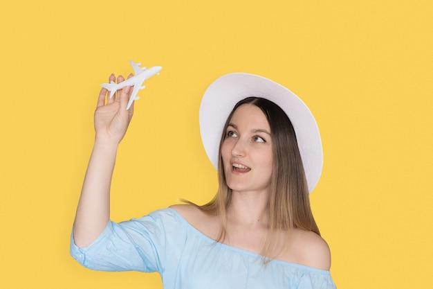 おもちゃの飛行機で遊ぶ若い女性の笑みを浮かべてください。