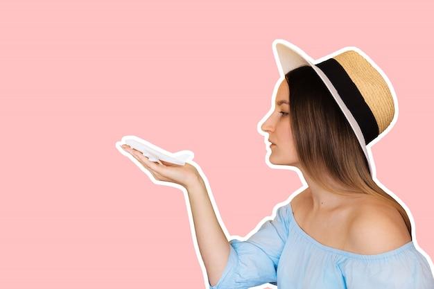 ピンクに分離された飛行機グッズモデルを保持している若い女性