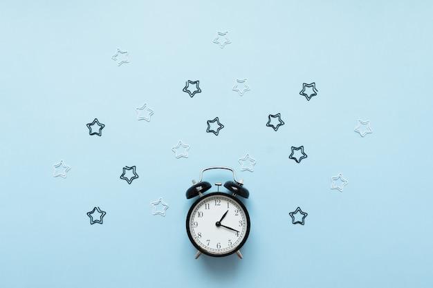 青色の背景に分離された目覚まし時計