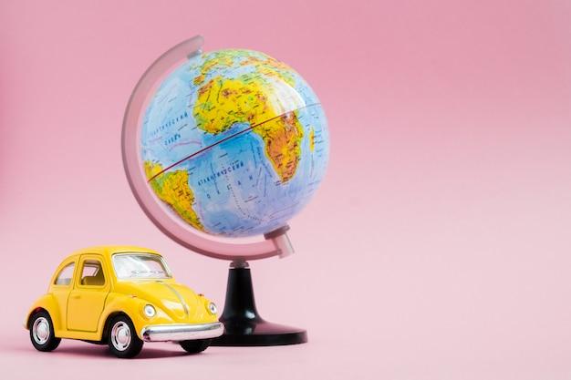世界グローブ球とかわいい黄色の小さなレトロな車