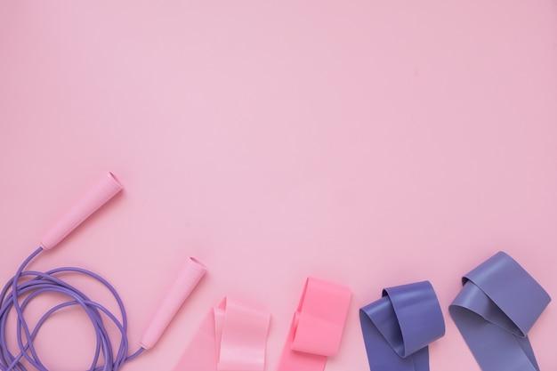 Прыжок или скакалка и фитнес-резинка на розовом фоне. фитнес-тренд.