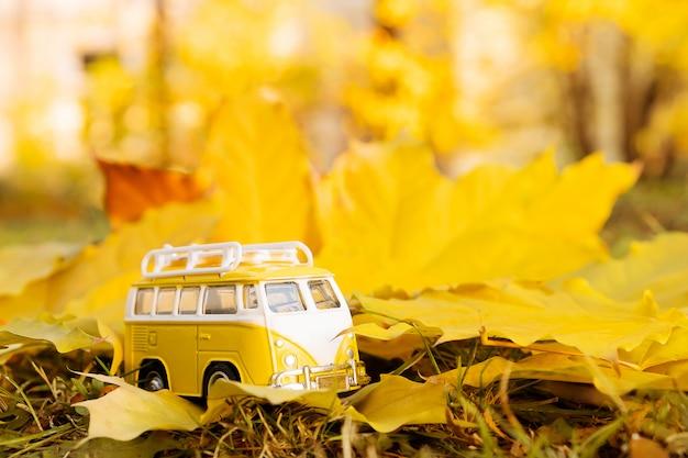 秋のカエデの葉に秋のレトロな黄色のバンバス。面白いレトロなおもちゃの車。秋の旅行や休暇の概念