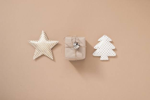 Рождественская композиция. рождественская подарочная коробка, звезда и новогодняя елка на пастельном бежевом фоне