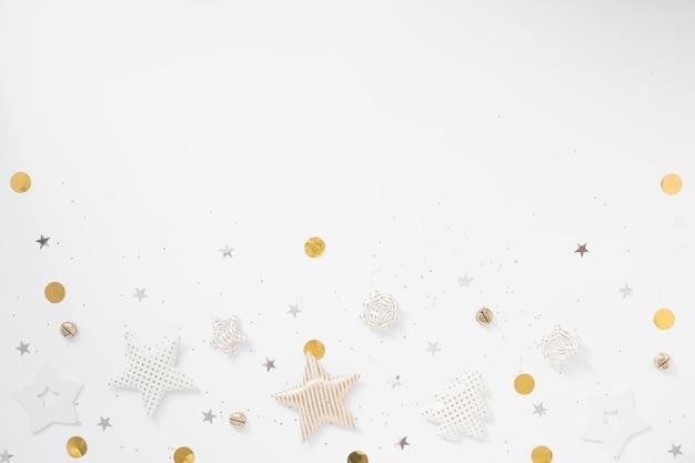 クリスマスの背景。金色の星、鐘、白い背景の上の弓。フラット横たわっていた、トップビュー、コピースペース