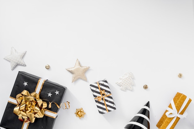 Стильное новогоднее украшение. подарки, шляпы, черные и золотые украшения на белом фоне